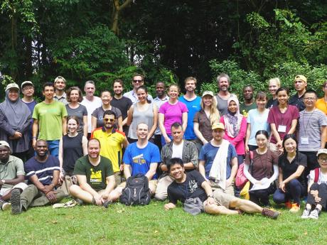 A group photo of the 53 workshop participants, assembled in 2 rows, some standing, others sitting, in front of cluster of trees.